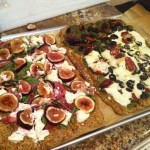 Left toppings: figs, goat cheese, fresh arugula, drizzled in honey. Right: fresh walnut pesto sauce, sun dried tomatoes, fresh mozzarella cheese and black olives.